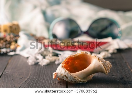 setting summer vacation. shells, pareo on the wooden background - stock photo