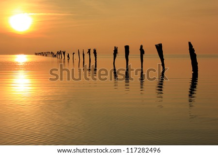 Setting sun above a line of fence posts, Great Salt Lake, Utah, USA. - stock photo