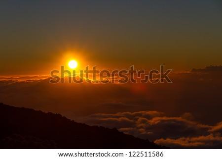 Setting sun above the clouds at Haleakala National Park, Maui, Hawaii - stock photo