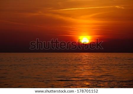 Setting sun in cloudy sky at the sea - stock photo