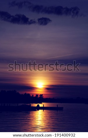 Setting sun over a lake with a silhouetted boat docked on the water.  Silhouetted trees are seen against the sky.  Processed and toned for a vintage faded retro look.  - stock photo