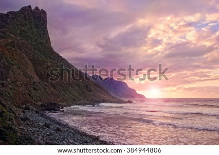 setting sun shining through clouds at volcanic black pebble beach on Atlantic coast in Anaga mountains, Tenerife, Canary islands, Spain - stock photo