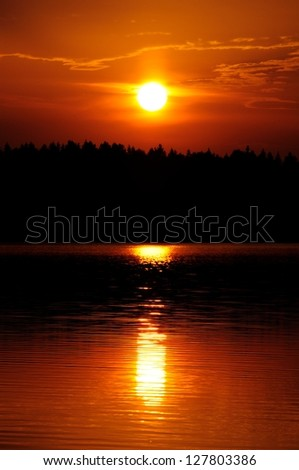 Setting Sun with Ray Path of Light on Water - stock photo