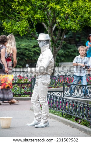 SEVASTOPOL, RUSSIA - JUNE 13:  Mime artist performs as living statue for tourists. Sevastopol 2014. Silver man - stock photo