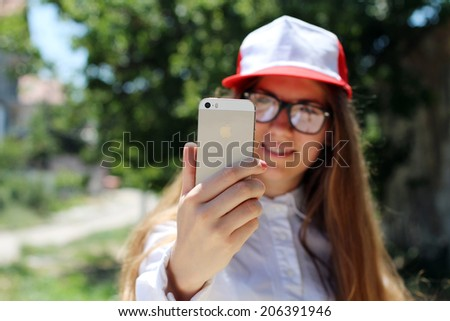 """SEVASTOPOL, UKRAINE- JULY 20, 2014: Girl taking a self portrait on Apple Gold iPhone 5S. In 2013, the word """"selfie"""" included in the online version of the Oxford English Dictionary. - stock photo"""