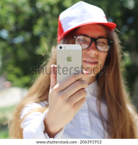 "SEVASTOPOL, UKRAINE- JULY 20, 2014: Girl taking a self portrait on Apple Gold iPhone 5S. In 2013, the word ""selfie"" included in the online version of the Oxford English Dictionary. - stock photo"