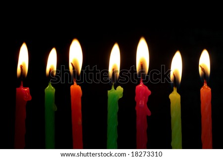 seven birthday candles with black background