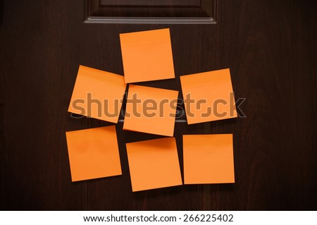 Seven blank sticky notes on the wooden door - stock photo