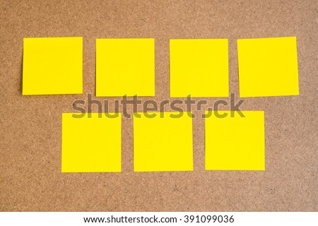 Seven blank yellow sticky notes on brown wood board - concept of business work, education, idea from team
