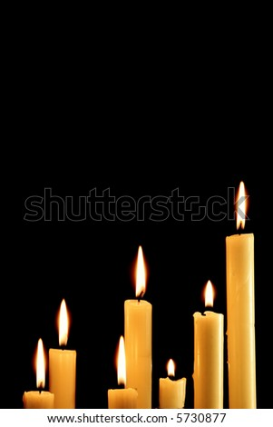 Seven burning candles over a black background