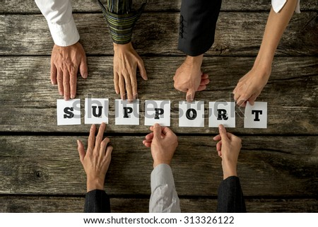 Seven business people holding white cards with letters to assemble the word SUPPORT on textured wooden desk. Conceptual of teamwork, cooperation and customer service. - stock photo