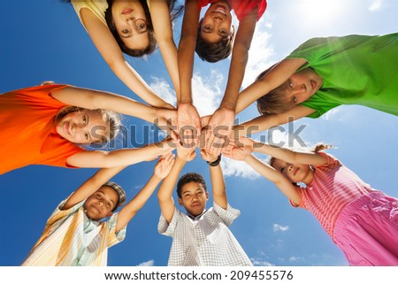 Seven children put arms in star shape - stock photo