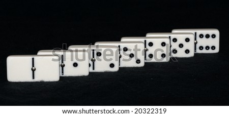 seven dominoes arranged in a line - stock photo
