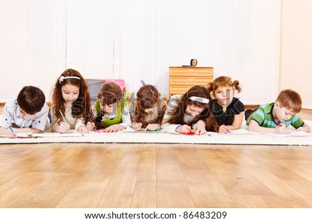 Seven friends lie in room, drawing - stock photo