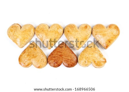 Seven gingerbread hearts in two rows on white background. One is darker than the others. - stock photo
