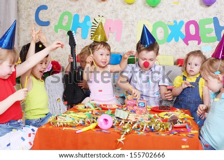 Seven happy little kids eat cake at red table at birthday party. Inscription Happy Birthday on wall. - stock photo