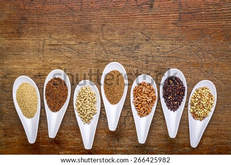 seven healthy, gluten free grains (quinoa, brown rice, amaranth, teff, buckwheat, sorghum. kaniwa), top view of small spoons against rustic wood with a copy space - stock photo