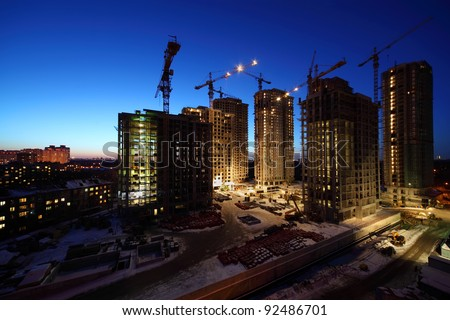 Seven high buildings under construction with cranes and illumination at night - stock photo