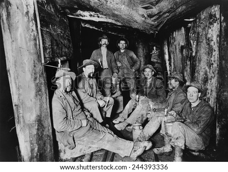 Seven miners pose for a photograph after lunch in the Last Chance Company mine in the Coeur d'Alene region of Idaho. The region was rich in silver, lead, gold and copper. Ca. 1910.