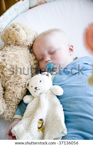 Seven month old baby sound asleep in his crib - stock photo