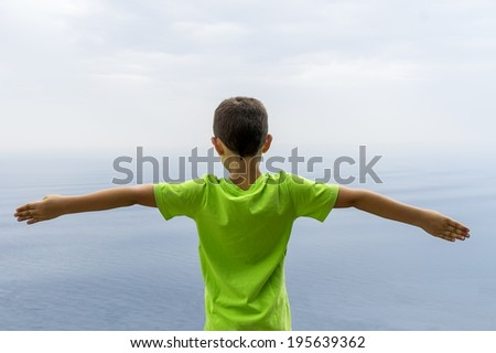 Seven old boy open arms in front of the sea