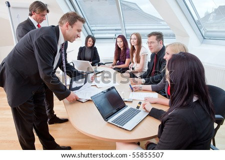 seven people having a meeting in the conference room - stock photo
