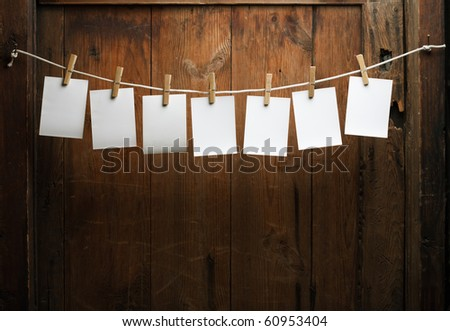 seven photo paper attach to rope with clothes pins on wooden background - stock photo