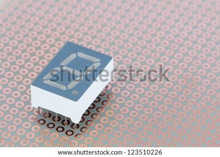 Seven segment led single digit display on a copper breadboard - stock photo