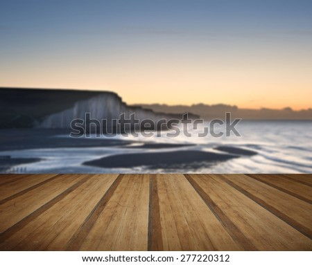 Seven Sisters chalk cliffs in England during Winter sunrise with wooden planks floor - stock photo