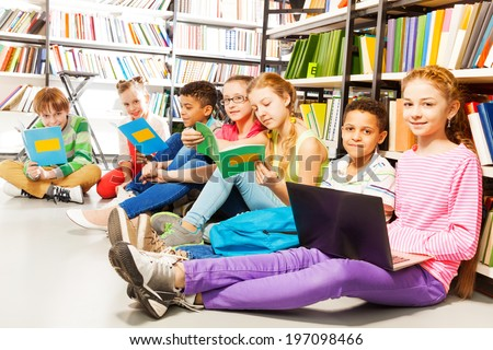Seven smiling children sitting in a row on floor - stock photo