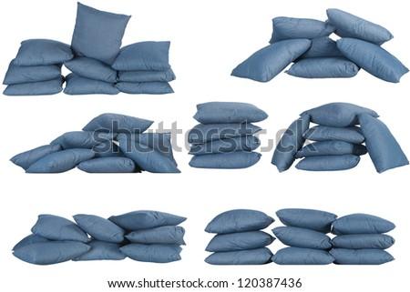 seven stacks of blue denim pillows isolated on white - stock photo