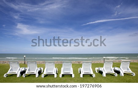 Seven stylish beach chairs on green grass beside sand beach and blue sky in the south of Thailand.  - stock photo