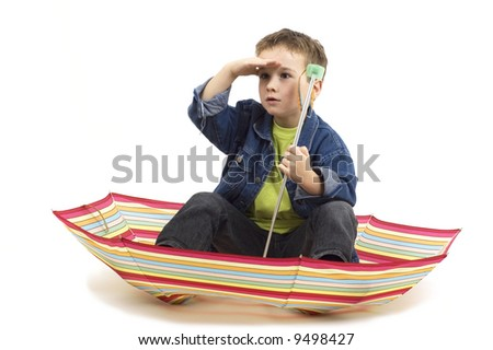 Seven year old boy sitting in an umbrella, playing like it's a boat.