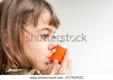 Seven year old girl is breathing asthmatic medicine healthcare inhaler - stock photo