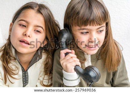 Seven year old girl talking on the old vintage phone and her sister eavesdropping her conversation. White background. - stock photo