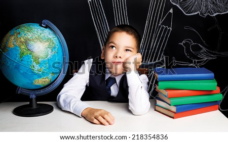 seven year old school boy sitting by the table and feeling bored - stock photo