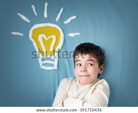 seven years old boy and a bulb near. Child with an idea - stock photo