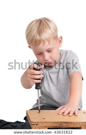 Seven years old boy using a screw-driver - stock photo
