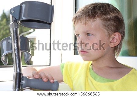 Seven years old boy with crutches sadly looks out of the window - stock photo