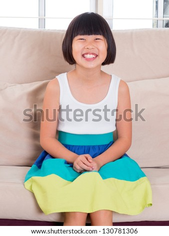 Seven years old Southeast Asian child sitting on sofa at home with happy face - stock photo