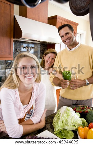 Seventeen year old girl in kitchen with parents in background - stock photo