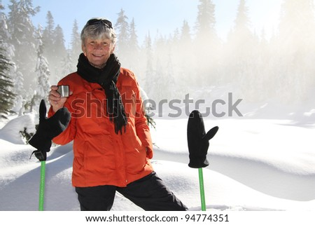Seventy year old lady having fun snowshoeing on Mount Seymour - stock photo