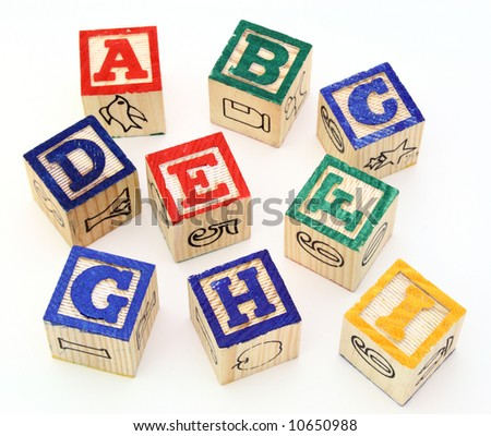 several alphabet blocks scattered on a white surface - stock photo