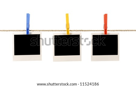 Several blank polaroid style instant camera photo prints hanging on a rope or string isolated against a white background.  Space for copy. - stock photo