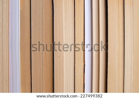 Several books arranged side-by-side on a shelf - stock photo