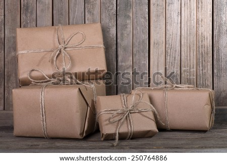 Several brown wrapped packages on a wood background - stock photo