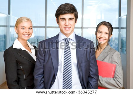 Several business partners looking at camera with successful man in front - stock photo