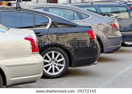 Several cars parked in a parking lot - stock photo