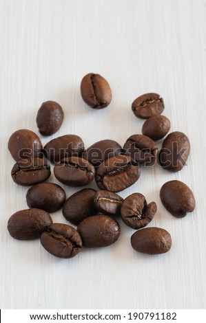 several coffee beans on white wooden table - stock photo