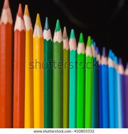 Several colored pencils standing on a dark background - stock photo